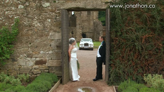 Lynda and Andrew Aberdour Castle wedding - newlyweds standing at walled gate