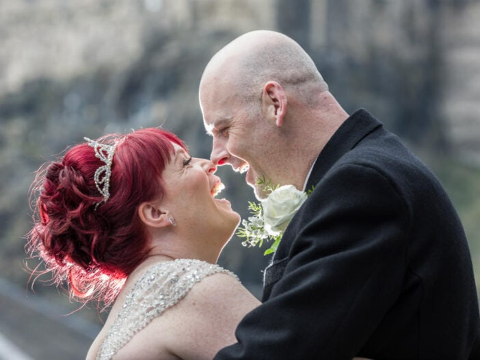 newlyweds touch noses in the Vennel with Edinburgh Castle in the background