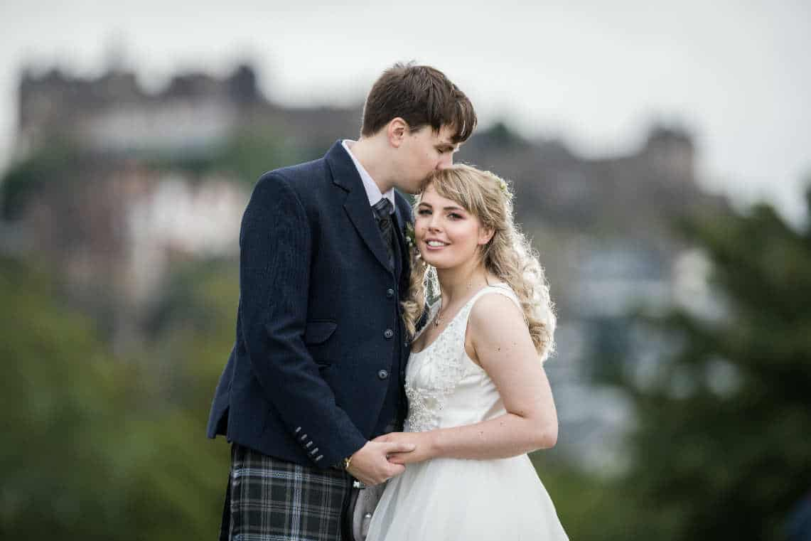 posed photo of groom kissing bride's head with Edinburgh castle in background
