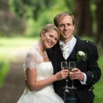 newlyweds raise a toast beneath the giant Redwood trees by Carberry Tower wedding photographer