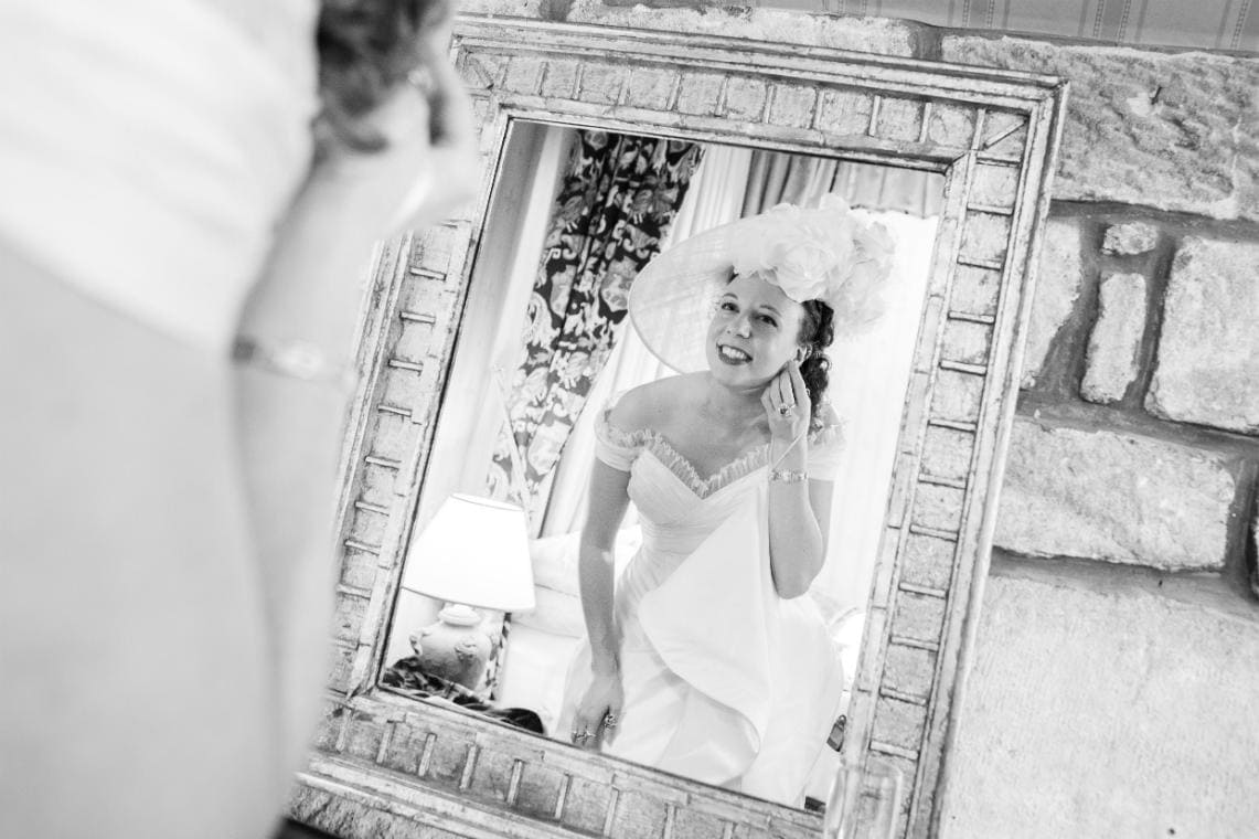 bride puts in her earrings in front of a mirror in one of the castle's suites