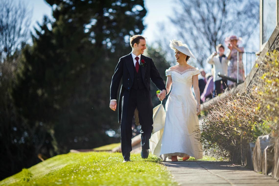 newlyweds walking together on a path in the castle grounds