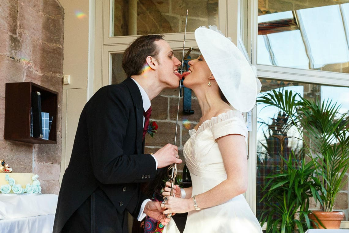 newlyweds licking the sword after cutting the cake in The Orangery