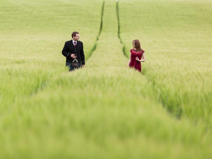 newlyweds walking along the tracks through a corn field near the castle