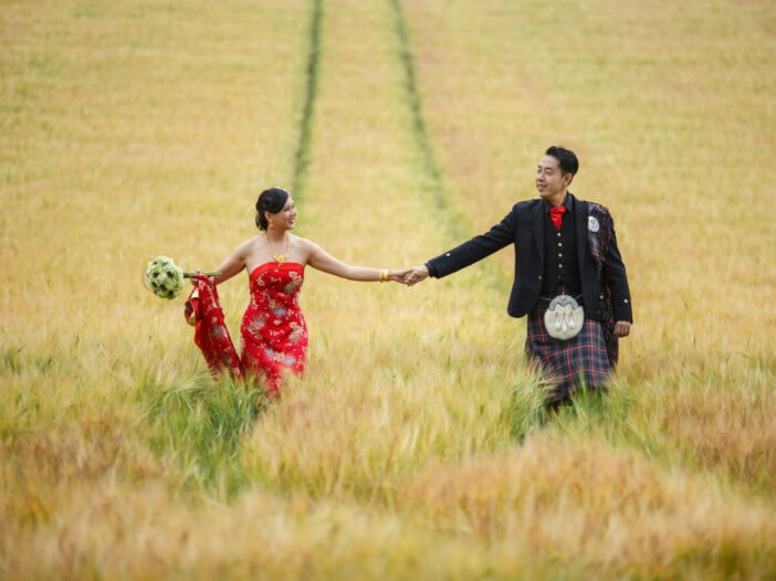 Chinese bride wearing a red dress holds her husband's hand as they walk through a field