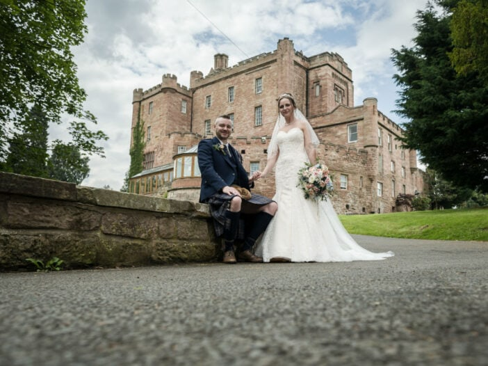 Bride and Groom with Dalhousie castle in the background.