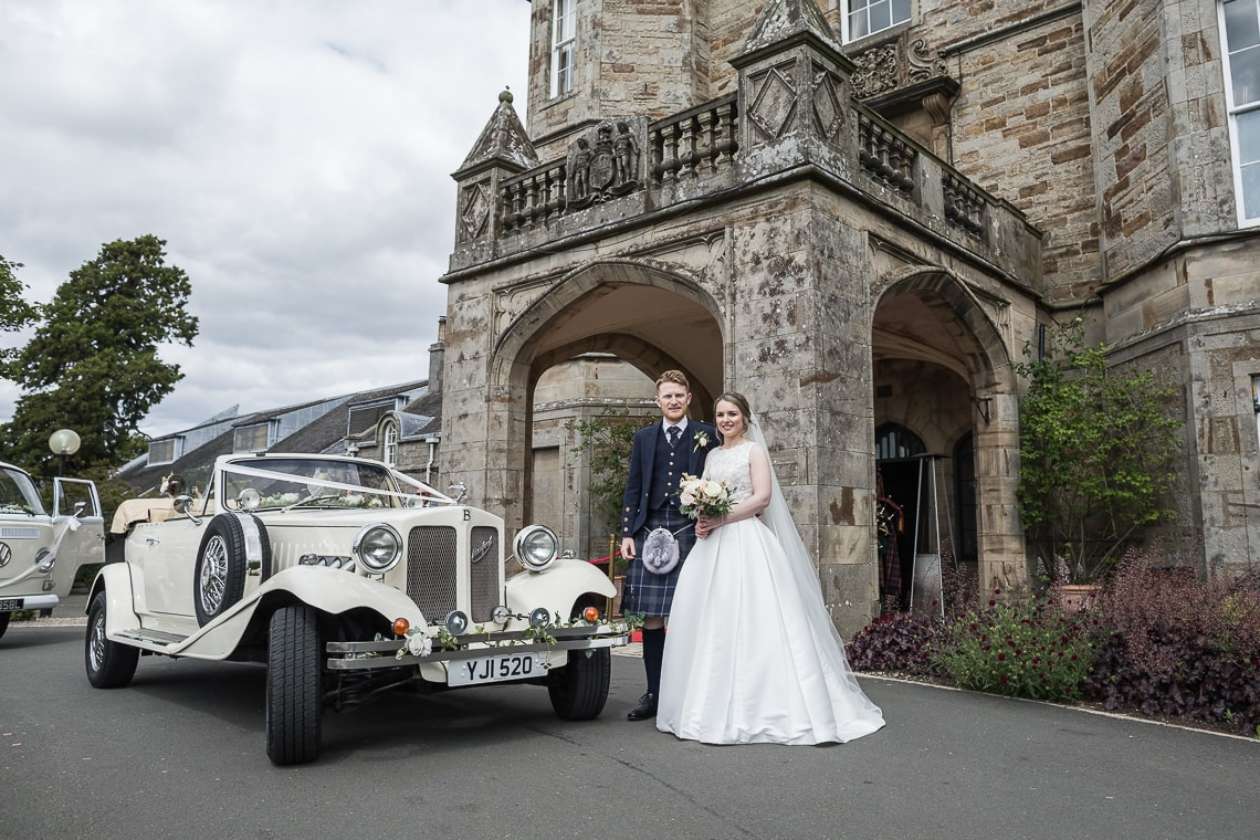 newlyweds standing next to a Beauford card at the hotel entrance