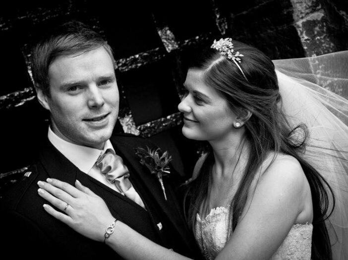 newlyweds embrace outside the Auld Keep