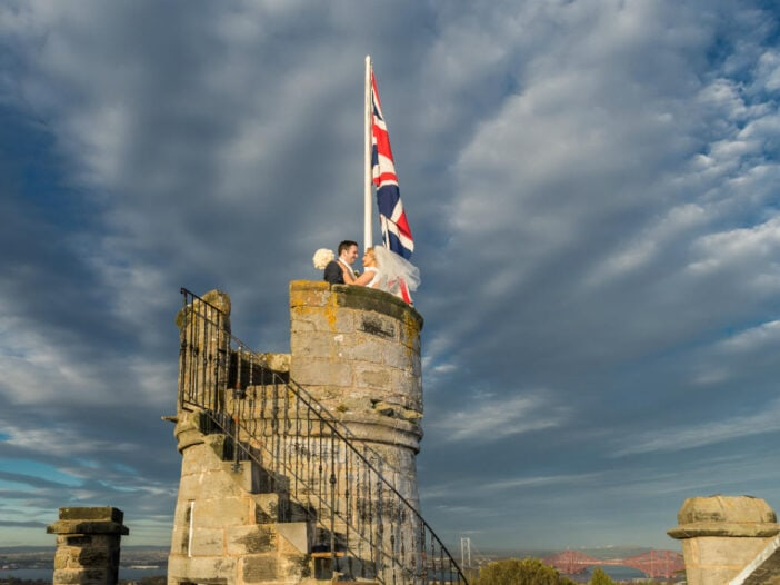 newlyweds embrace next to the Union Jack on the roof of the Auld Keep