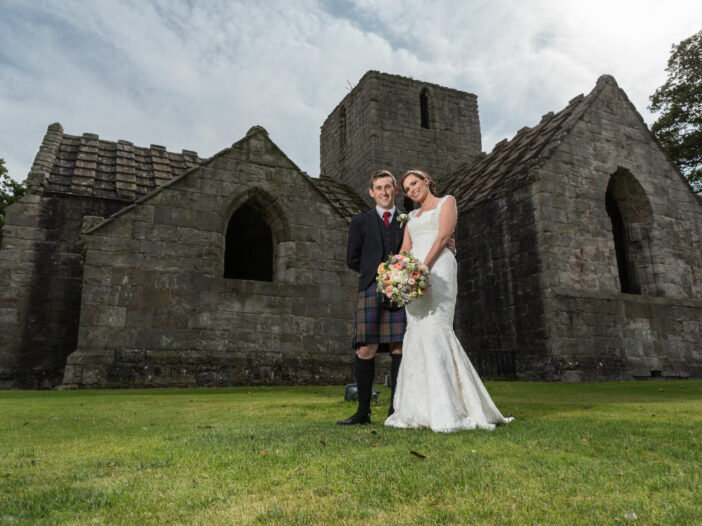 newlyweds standing in front of Dunglass Collegiate Church