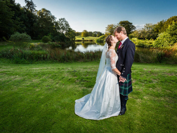 Dunglass Estate wedding Katie and Tom kiss in front of the pond