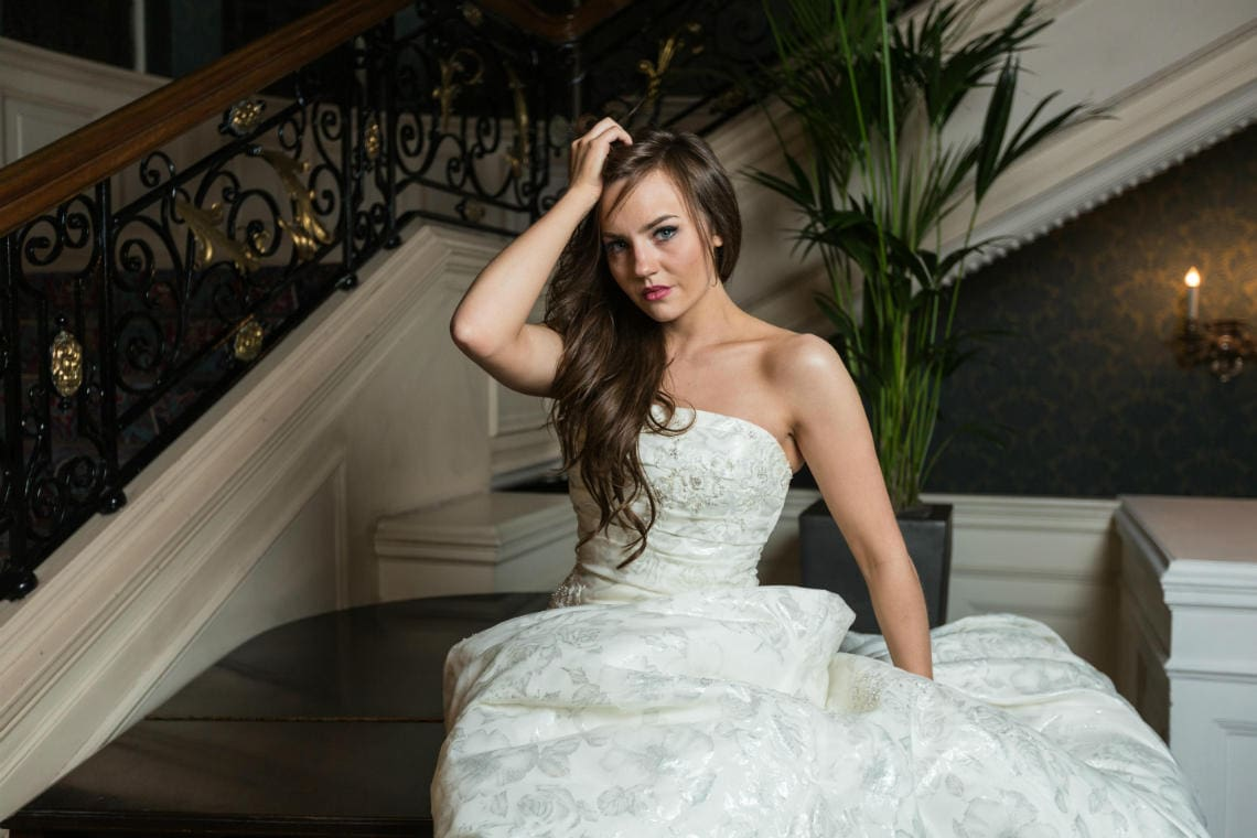 bride sitting on the piano at the foot of the staircase in the Balmoral Hotel