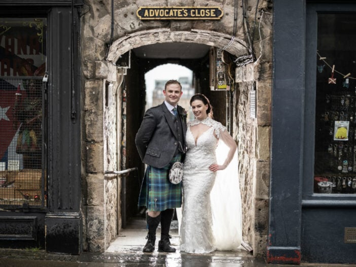 Newlyweds standing in the entrance to Advocate's Close in Edinburgh