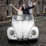 Eskmills Venue Wedding - Blythe and Dean standing waving in a convertible VW Beetle
