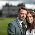 newlyweds on the golf course with the Dalmahoy Hotel in the background