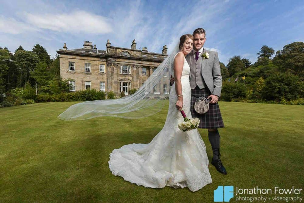 Newly-wed flowing veil photo  in front of Balbirnie House