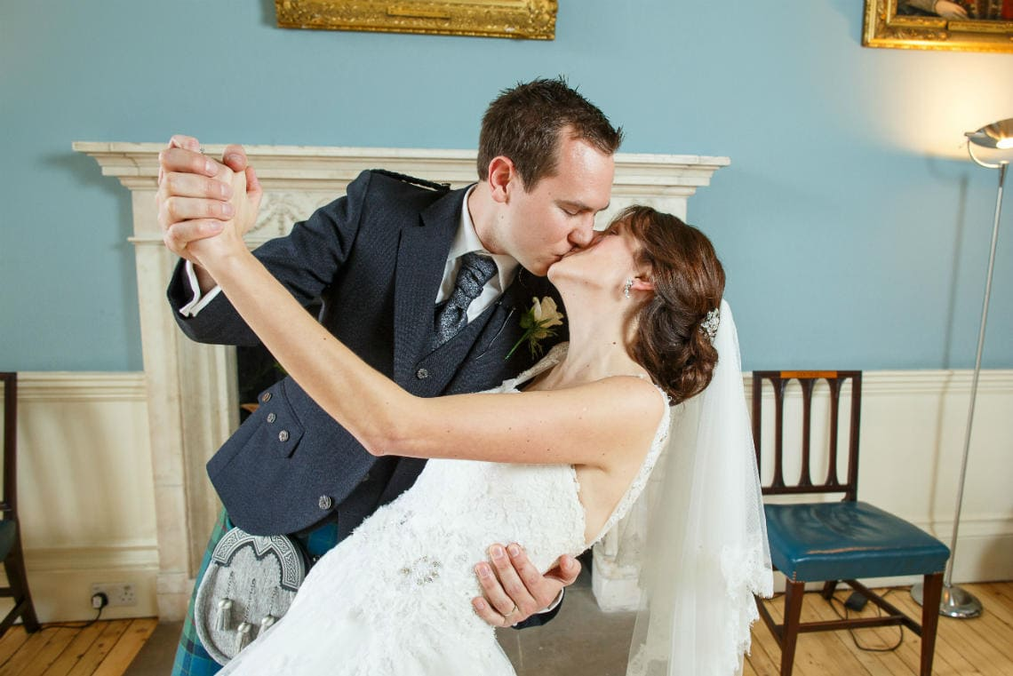 newlyweds kissing in the Cullen Suite