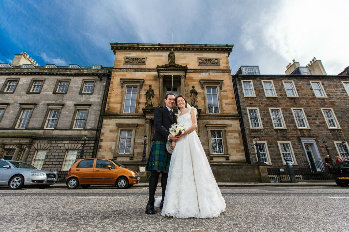 newlyweds standing outside the Royal College Of Physicians Of Edinburgh on Queen Street