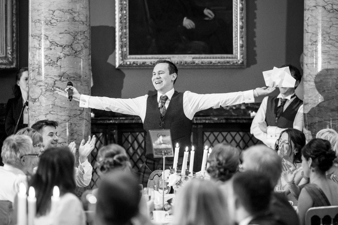 groom with raised arms during his speech in the Great Hall