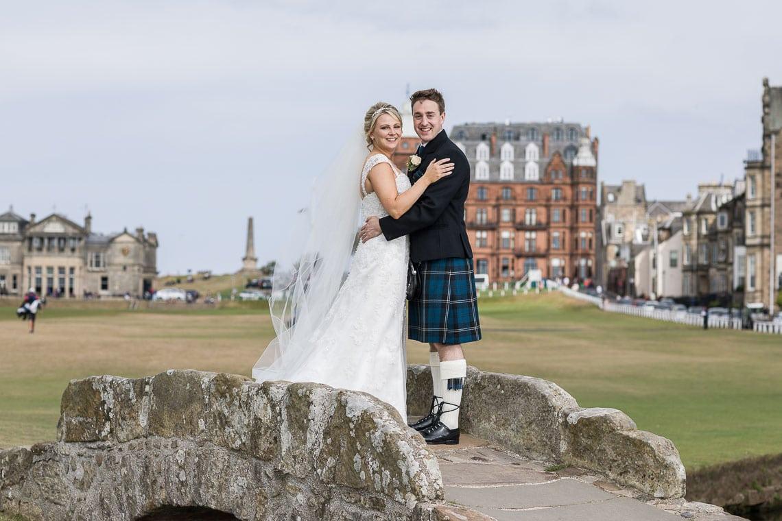 newlyweds embrace on Swilken Bridge for St Andrews wedding photographer