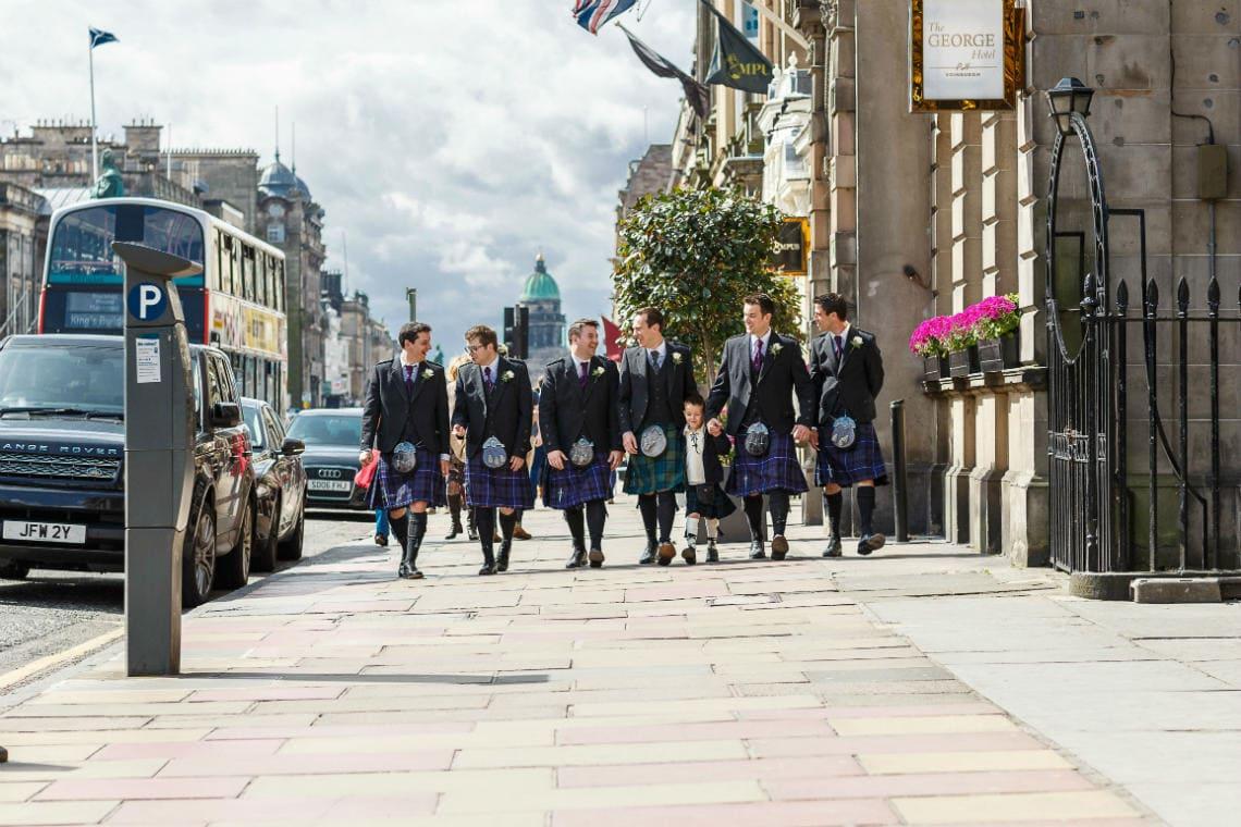 groom and groomsmen wearing kilts walking along George Street