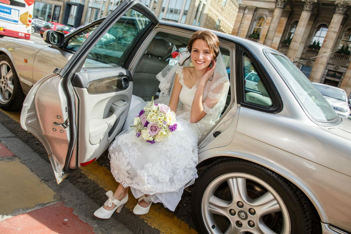 bride in white dress getting out of a Jaguar wedding car on George Street