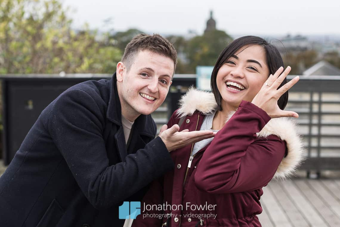 Surprise Engagement Proposal in Edinburgh - Matt and Rona smiling on rooftop terrace with Rona wearing engagement ring