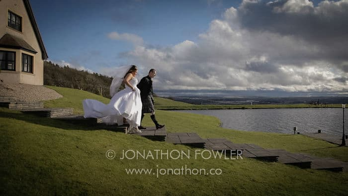 Jemma and Allan's wedding at The Vu Bathgate - newly-weds walking to the jetty