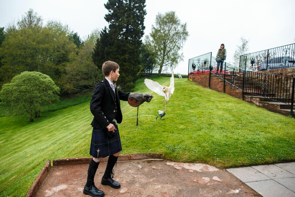 bride's son wearing kilt outfit and leather gauntlet receives owl on the patio