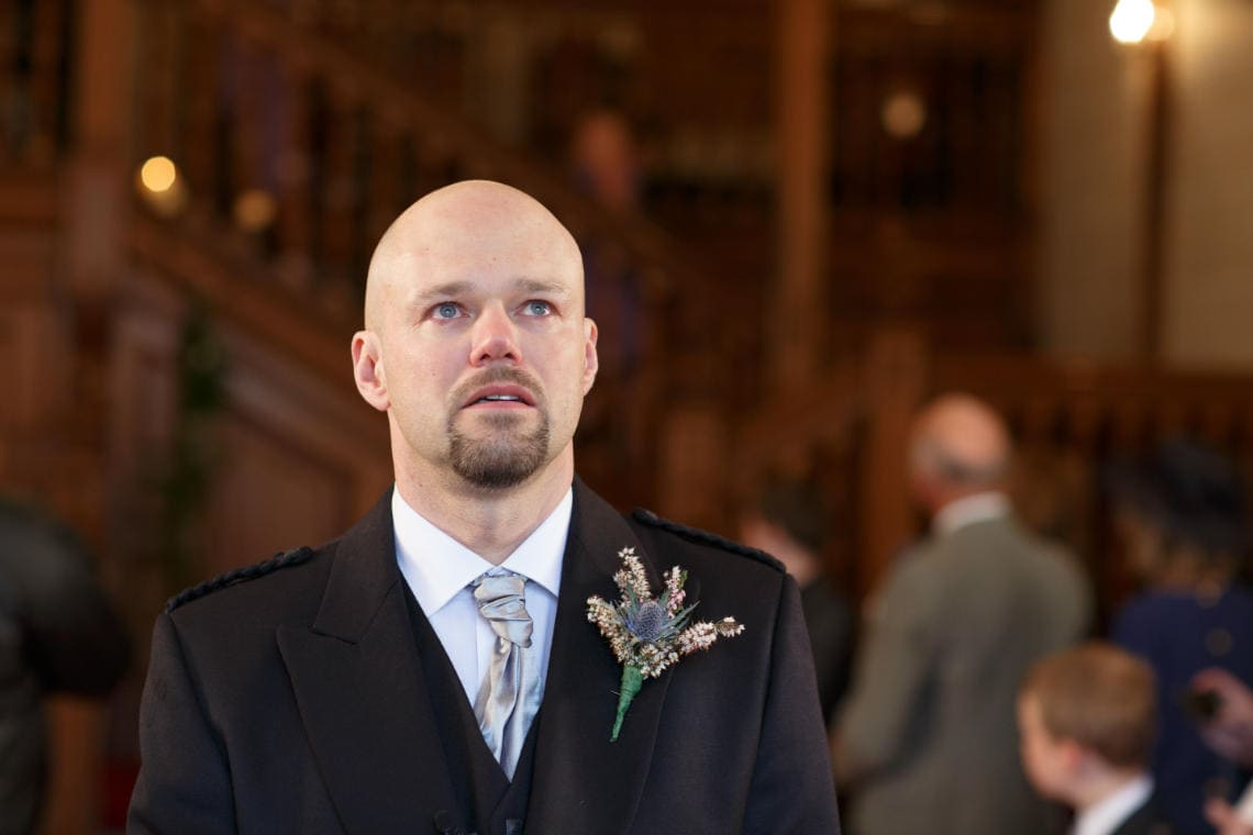 teary-eyed groom waits for the bride in the chapel