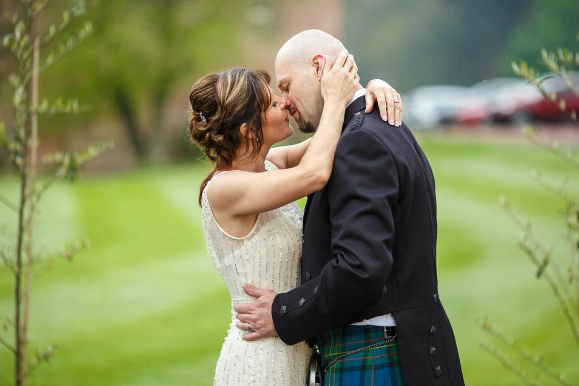 newlyweds embrace on the lawn in front of the castle