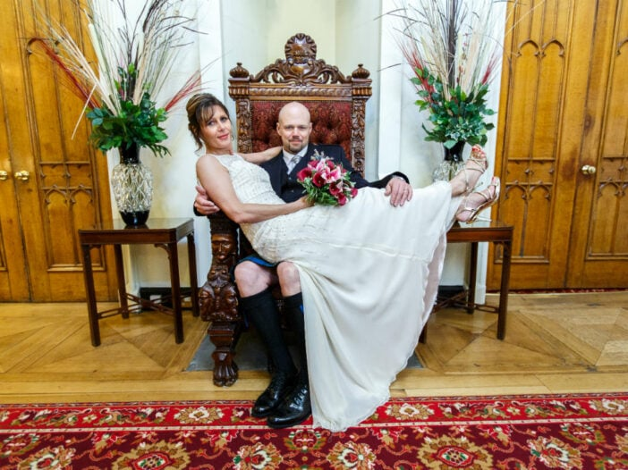 bride sits on groom's lap on the throne in the reception area